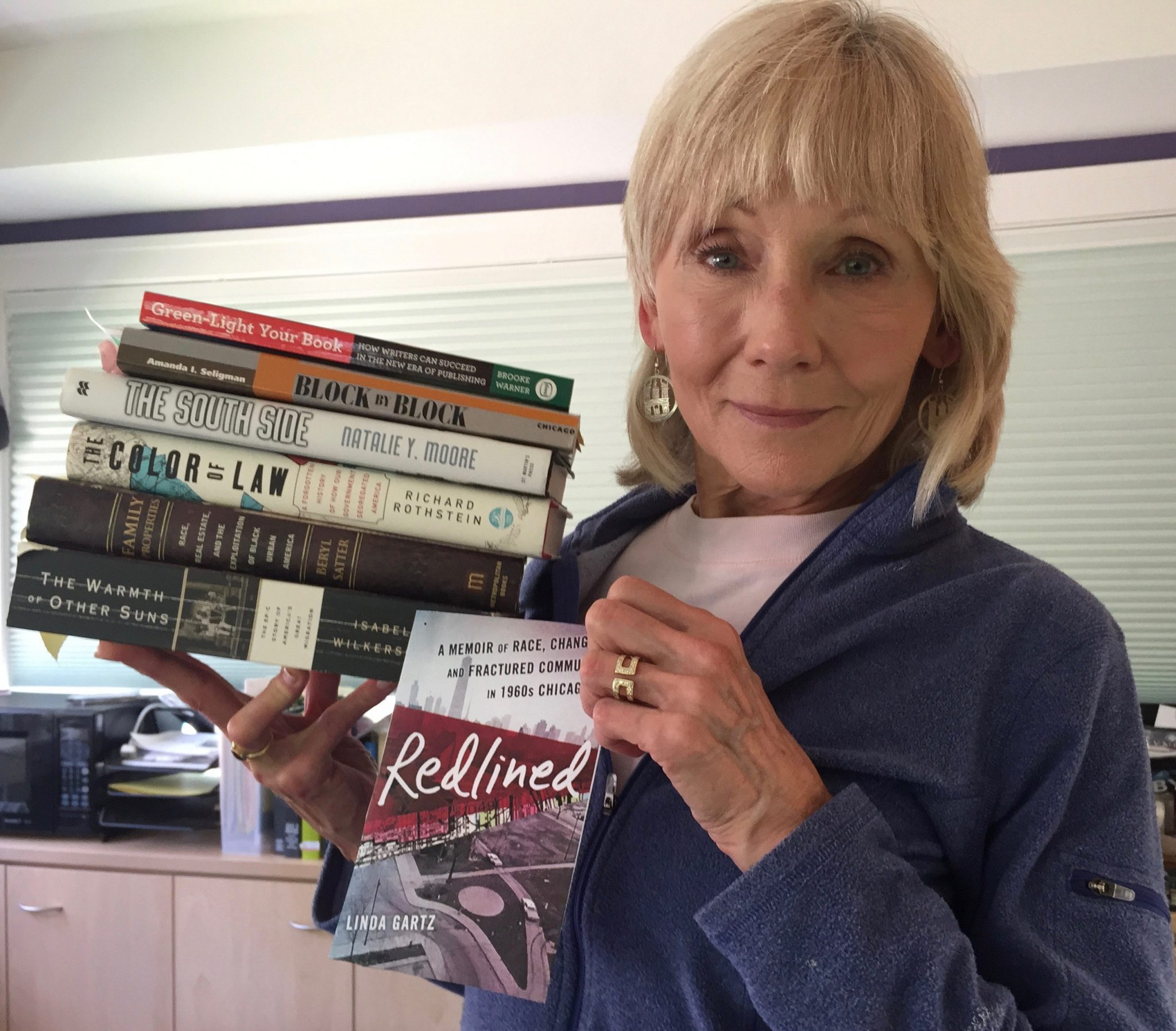 Author Linda Gartz holds many books she used to do research for her book, Redlined: A Memoir of Race, Change, and Fractured Community in 1960s Chicago.