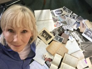 Author, Linda Gartz, sitting among a slew of family archives: photos of various sizes, diaries, letters, etc.