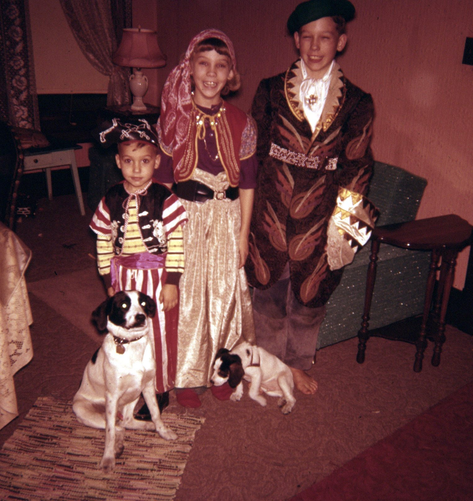 three siblings in 1958 pose in their self-created Halloween costumes in 1958. A 5 year-old boy is dressed in a pirate's hat, sash and striped pants; the girl, Linda, is dressed in the image of a gypsy, with bandana, flowing skirt, sash at waist, colorful vest; the oldest boy, 12, is dressed in a buccaneer's hat, an oversized brocaded jacket, shimmery shirt with lace cuffs; two spotted dogs, father & son, named Buttons and Bows, are at their feet; Bows is a puppy, about 8 weeks old.
