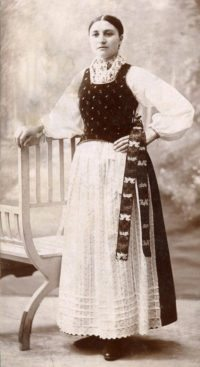 A 1910 photo of Elisabetha (Lisi) Ebner in traditional Romanian costume, long white skirt, fitted jumper-like dark top of a white blouse with blouse sleeves. A narrow scarf is wrapped at her waist, hanging to knee-length. Her hair is pulled back and parted tightly down he middle. Her left hand is on her hip and her right hand rests on a piece of furniture. She has intense, black eyes and stares into the distance. She's 22 years old, proud, and beautiful.
