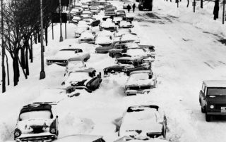 Cars are strewn about and abandoned, mired in the snow