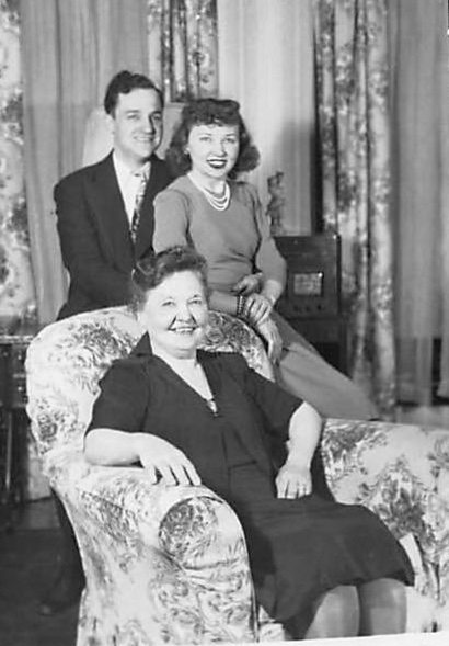 Very attractive young, married couple stands behind a large comfy chair with flowered print in which sits the mother of the young woman.