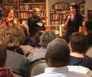 Ron Stallworth shows his red KKK card from the 1970s to an audience while his wife, Patty, and bookstore owner, Nina Barrett, look on. Books on shelves in the background. Heads of lots of audience members in foreground