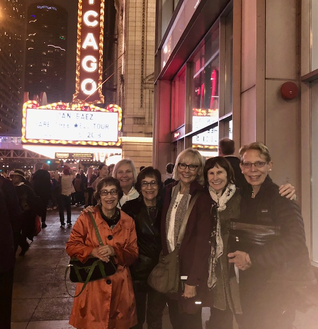 """Six women pose in front of the marquee of the Chicago Theater emblazoned with the name: """"Joan Baez; Fare Thee Well Tour"""""""