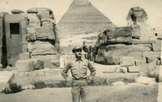 Handsome World War II navigator stands with hands on hips in front Egyptian Pyaramid