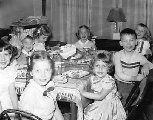 Birthday party 1954 for a five-year-old girl with children around a table and a birthday cake with candles